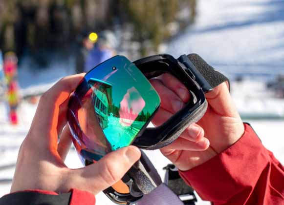A person changing a ski goggle lens