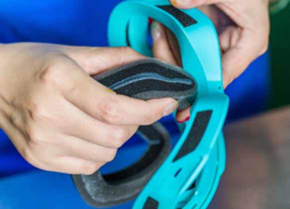 A person lining a ski goggle frame with foam