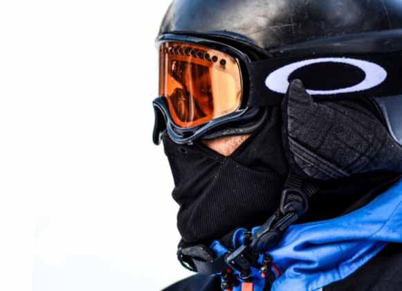 A person wearing ski goggles with orange-colored lenses