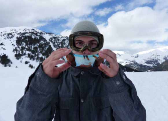 A skier holding a detachable goggle lens