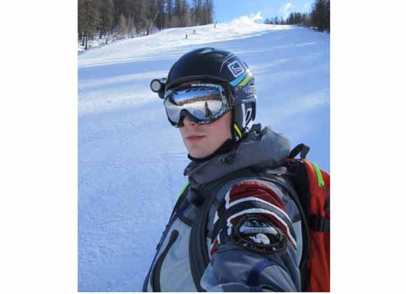 A skier in gear wearing mirror lens ski goggles