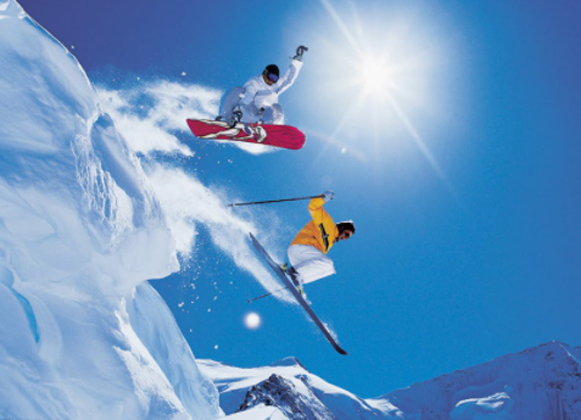 A snowboarder and a skier midair