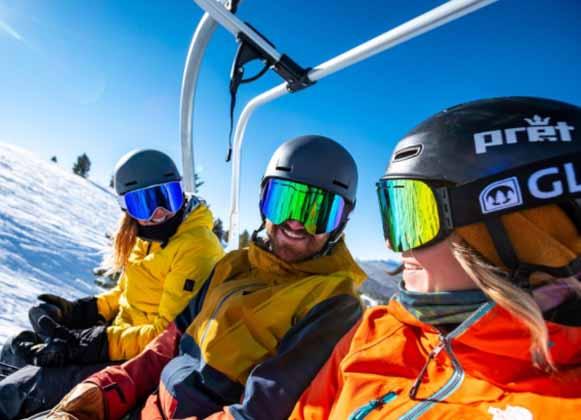 Skiers wearing helmet-compatible ski goggles