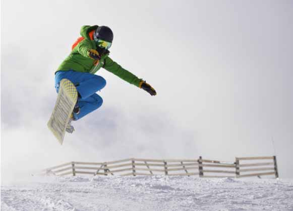 A snowboarder mid-air on a jump