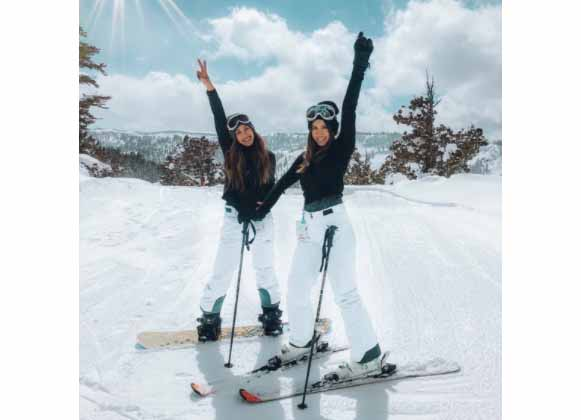 Two women out in the snow wearing black and white ski gear